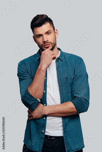 Taking time to think. Charming young man looking at camera and keeping hand on chin while standing against grey background