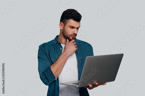 Considering next step. Thoughtful young man using laptop and keeping hand on chin while standing against grey background