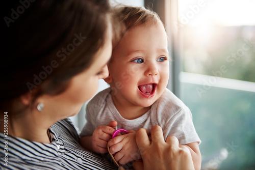 Leinwandbild Motiv Loving mum hugging her adorable baby girl
