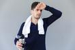 Leinwanddruck Bild - Tired sportsman holding water bottle