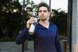 Leinwanddruck Bild - Handsome young sportsman drinking water