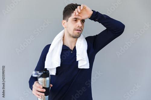 Leinwanddruck Bild Tired sportsman holding water bottle
