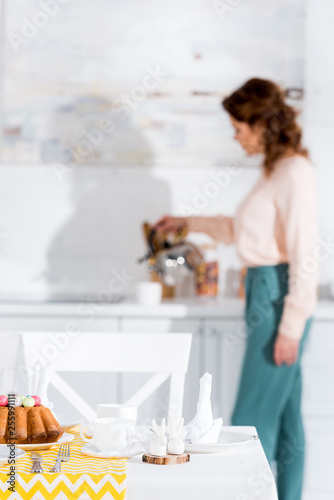 Leinwanddruck Bild Brunette woman with kettle and served table on foreground