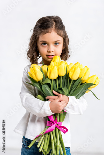 Leinwandbild Motiv Front view of cute curly kid holding tulips bouquet on white