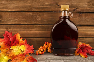 Maple syrup bottle on a wooden plank background. Maple leaves in decoration. Copy space for your text.
