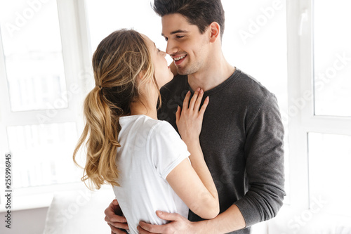 Portrait of european couple smiling and hugging together while standing near big window at home
