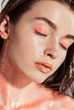 beautiful stylish girl covered in coral glitter posing with eyes closed - 255997396