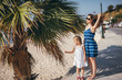Young mother running fingers through hair while standing on the street with her daughter near the palm tree