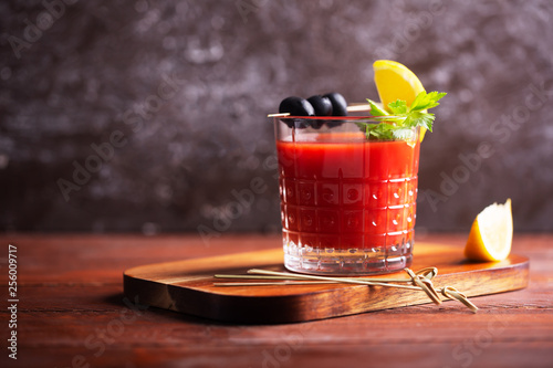 Cocktail Bloody Mary with ice, salt and snacks in glass on a wooden table - 256009717
