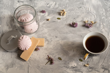 A cup of tea on a gray background, waffles, marshmallows. small flowers. flat lay
