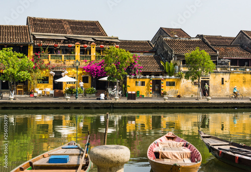 Foto Murales scene from the old historic town of Hoi An along the river with boats, lanterns, flowers and the gold yellow Hoi An buildings with tile roofs