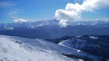 "Постер, картина, фотообои ""Wonderful time-lapse. Skiers and snowboarders on a ski slope of a background beautiful mountain landscape."""