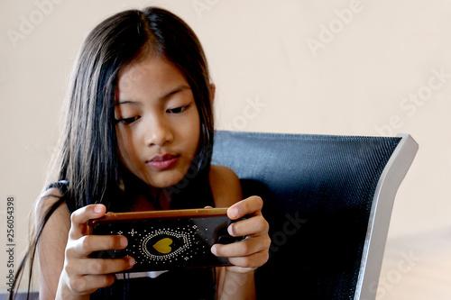 Petite fille asiatique joue avec un smartphone très concentrée