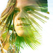 Double exposure close up of a young happy natural beauty and tropical leaves with rays of bright sunlight shining through them