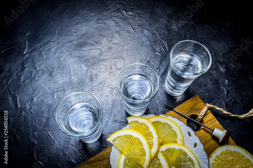 Strong alcohol poured into a glass. lemon slicing.