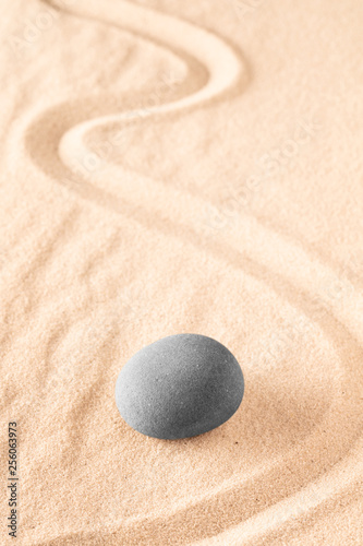 Raked sand and spa wellness healing stones. Zen buddhism meditation stone for concentration and relaxation through minimalism and purity. Spiritual background with copy space.