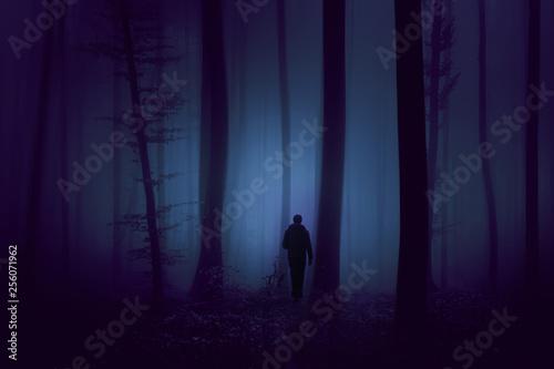 Leinwanddruck Bild Man walks in dark violet colored foggy forest