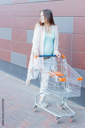 Pregnant woman is walking in the mall, soft focus background