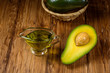 Half avocado fruit and avocado oil in a glass bowl on old rustic table. Healthy eating, diet, body care and hair care concept. - 256076318