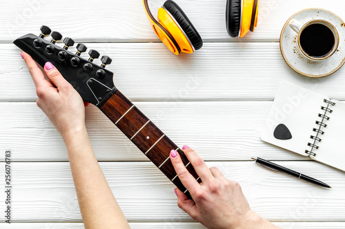 Professional dj instruments with headphones, guitar, notebook and coffee on wooden background top view