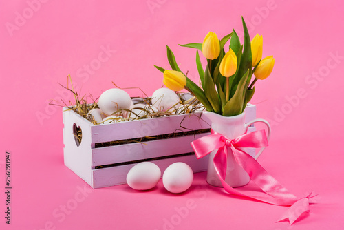 Easter. Eggs in a white wooden box with hay and yellow tulips in a white jug. Pink background. - 256090947