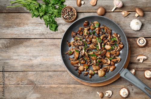 Frying pan of mushrooms on wooden background, flat lay with space for text - 256101945
