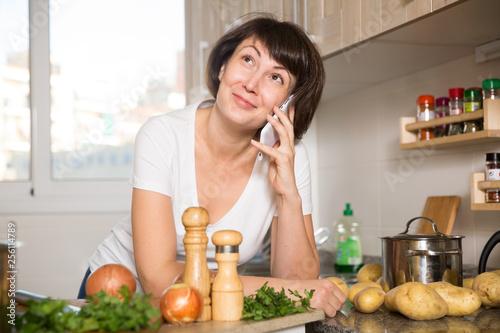 Leinwanddruck Bild Housewife talking on mobile phone