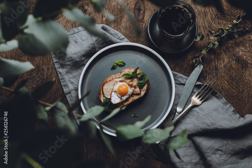 Ham and Fried Quail Egg Toast with Mustard and Basil on a dark wooden background, top view
