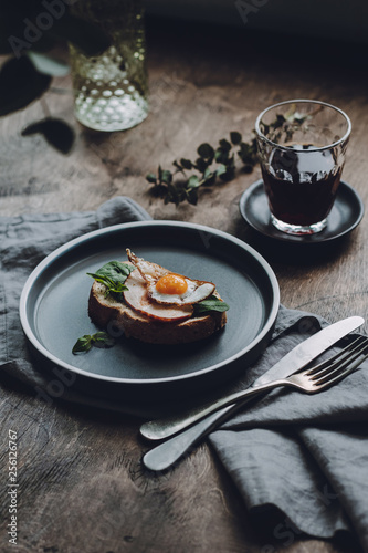 Ham and Fried Quail Egg Toast with Mustard and Basil on a dark wooden background, selective focus - 256126767