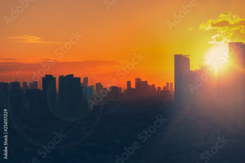Sunset view of city skyline with bright emotional and powerful energy from light.  First sunlight at dusk. © Travis