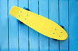Yellow skateboard on azure wooden background. Concept trend and youth hobbies