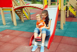 little boy on playground. playing child with mother on a slide