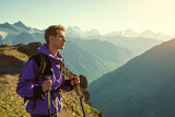 climber on trail in the mountains. a man with backpack in a hike