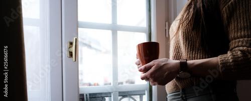 Frau steht am Fenster und hält eine Tasse in der Hand - 256166176