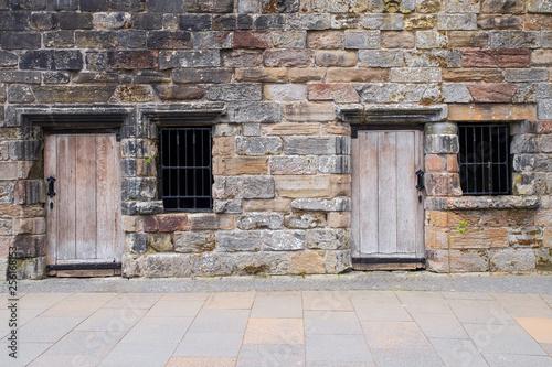 Leinwanddruck Bild Tuer und Fenster in einer Steinmauer