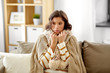 people, health and cold concept - sad sick woman in blanket and scarf at home