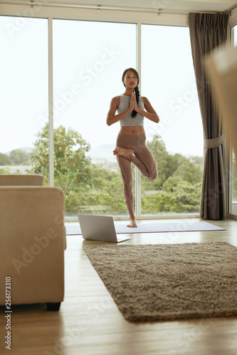 Foto Murales Girl practices yoga in tree pose, exercising at home in morning