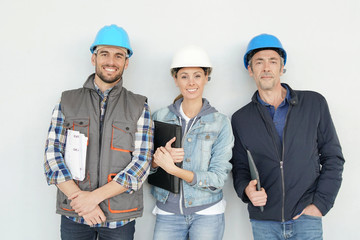 Mixed construction team smiling at camera on grey background © goodluz