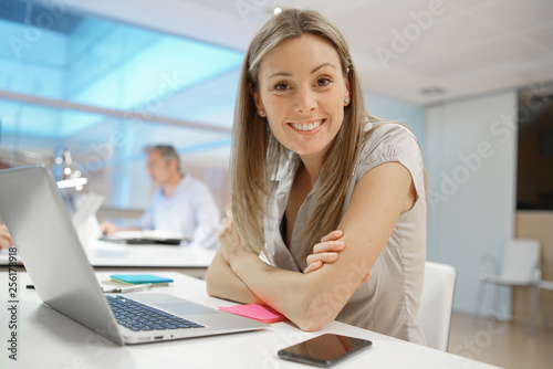 Smily businesswoman looking at camera in modern office