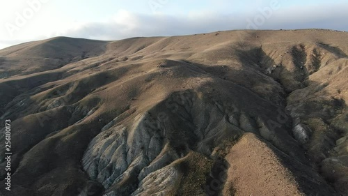 flight over a rocky hill to the horizon in the clouds top view shooting using a quadrocopter