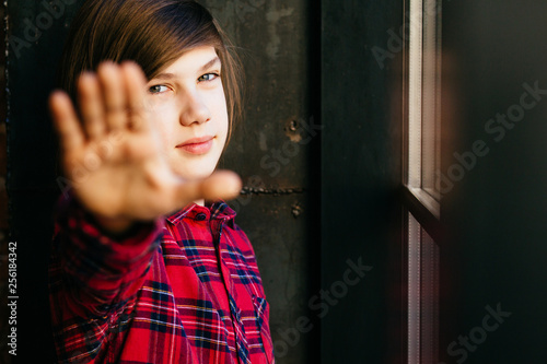 Portrait thoughtful caucasian teenager with long straight hairstyle showing stop sign with palm, looking at camera in dark modern loft interior. Child wthout parents, independent concept.