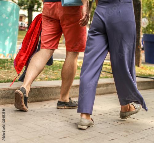Feet of people walking along the road