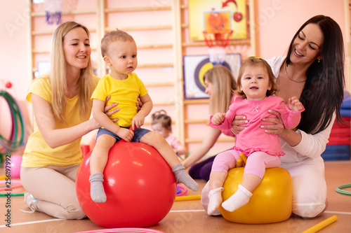 Leinwanddruck Bild Mothers with babies doing exercises with gymnastic ball in gym. Concept of caring for the child's health