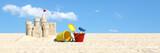 Sandburg und Sandspielzeug am Strand im Urlaub