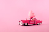 Retro toy car model with hearts on a pink background. The 14th of February. Valentine's day delivery concept. March 8, World Women's Birthday