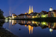 canvas print picture - Blick auf die steinerne Brücke und dem Dom St. peter an der Donau in Regensburg zur blauen Stunde im Mondlicht