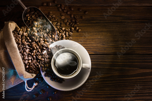 Coffee cup and coffee beans on wooden background. Top view. - Image