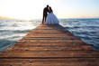 Wedding couple, bride, groom walking and posing on pier