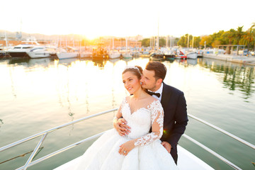 Beautiful wedding couple posing on boat at sea
