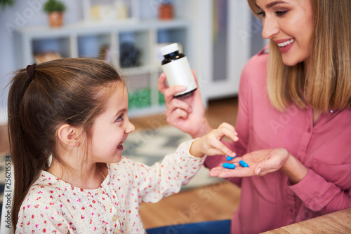 Young mum giving her little daughter the medicine © gpointstudio
